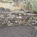 Dry stone retaining wall made from reclaimed sandstone