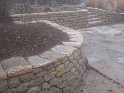 Dry stone retaining wall and flat cap stones