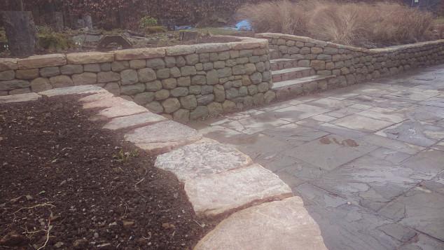 Dry stone retaining wall and flat cap stones